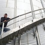 Farmer standing on outside ladder of grain bin